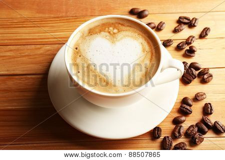 Cup of coffee latte art with grains on wooden table, closeup