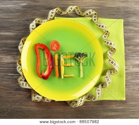 Word DIET made of sliced vegetables in plate with measuring tape on wooden table, top view