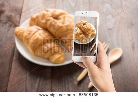 Taking Photo Of Fresh Baked Croissants On Wood Table