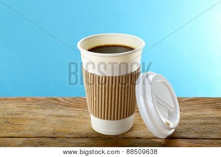 Paper cup of coffee on wooden table on blue background
