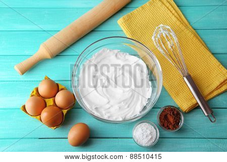 Whipped egg whites for cream on wooden table, top view