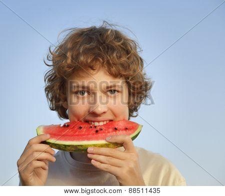 happy teenager eating watermelon in the garden