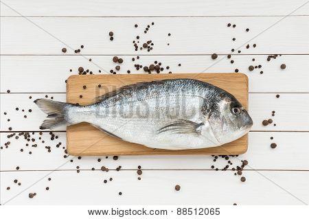 Fresh Dorado Fish On Wooden Cutting Board With Peppercorns