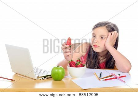A Little Girl Sitting At His Desk Eating A Strawberry