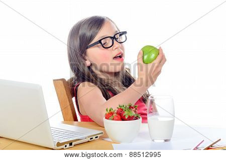 A Little Girl Sitting At His Desk Eating An Apple