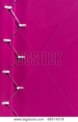 Pink tarpaulin of a trailer with lacing