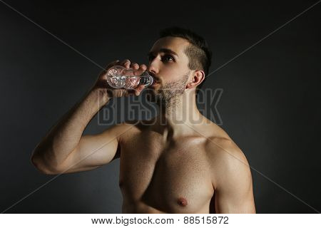 Muscle young man holding bottle of water on black background