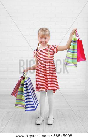 Beautiful little girl with shopping bags in room