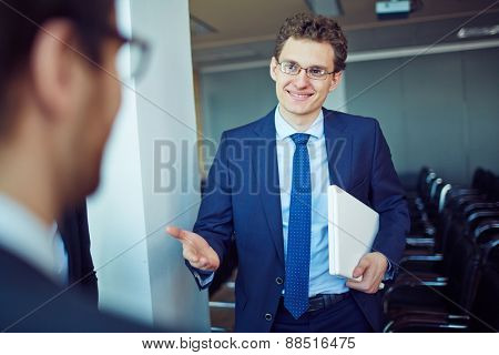 Elegant employee in suit and eyeglasses welcoming business partner