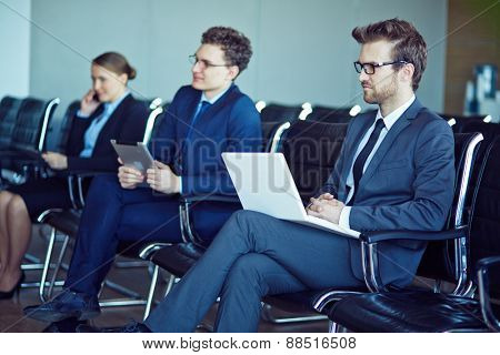 Row of elegant business people sitting at conference