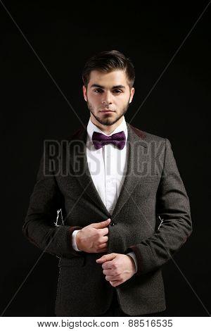 Elegant man in suit on dark background