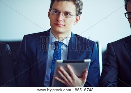 Elegant young businessman with touchpad looking aside