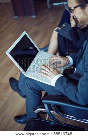 Male employee typing at working seminar or conference