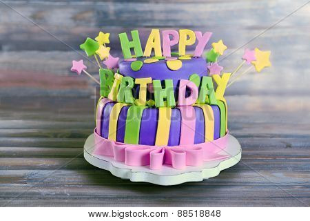 Delicious birthday cake on wooden background