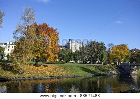 Autumn in Riga, Trees of park, city canal. Central building of University of Latvia in background.