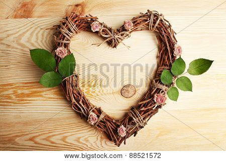 Wicker heart with dried roses and green leaves on wooden background