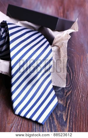Striped necktie in box on wooden background