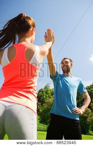 fitness, sport, training and lifestyle concept - two smiling people making high five outdoors