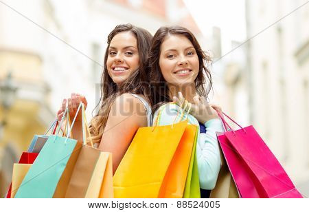 sale, shopping, tourism and happy people concept - two beautiful women with shopping bags in the ctiy