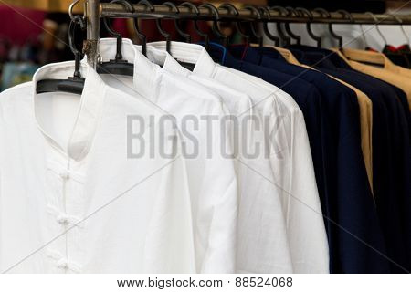 shopping, industry, sale and clothing concept - male oriental shirts on hanger at asian street market