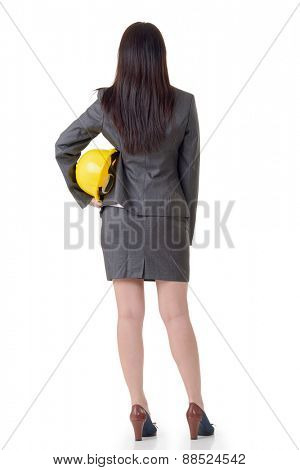 Business woman holding hat, full length portrait on white background.