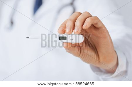 bright close up of male doctor with thermometer