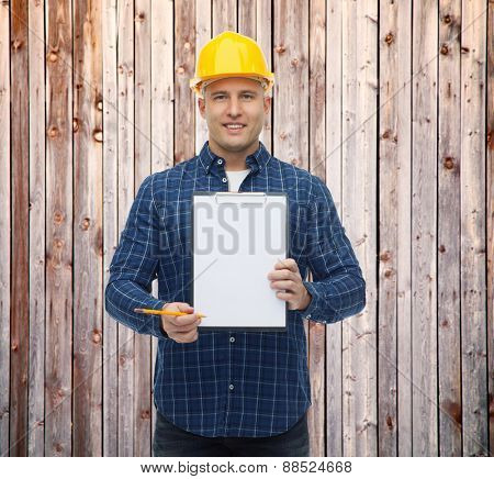 repair, construction, building, people and maintenance concept - smiling male builder or manual worker in helmet showing blank paper on clipboard over wooden fence background