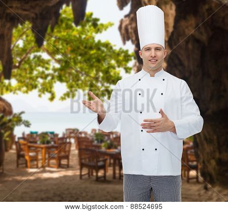 cooking, profession and people concept - happy male chef cook inviting over restaurant lounge on beach
