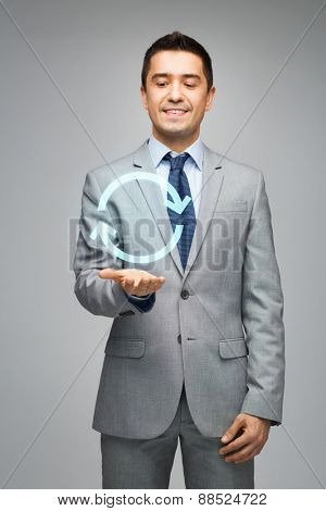 business, people, development and management concept - happy businessman in suit showing or holding circle arrow on palm