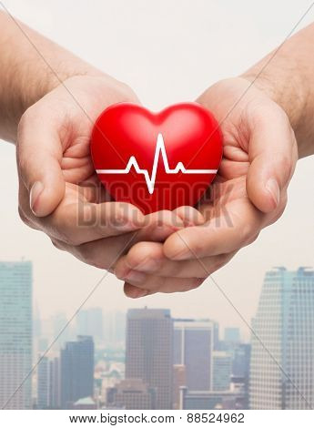 family health, charity and medicine concept - close up of hands holding red heart with cardiogram over city skyscrapers background
