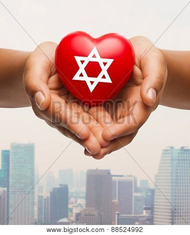 religion, christianity, jewish cummunity and charity concept - close up of female hands holding red heart with star of david symbol over city skyscrapers background