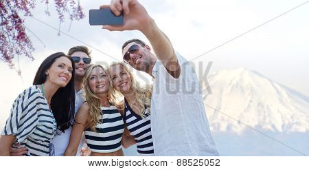 summer, asia, tourism, technology and people concept - group of smiling friends taking selfie with smartphone over fudjiyama mountain background