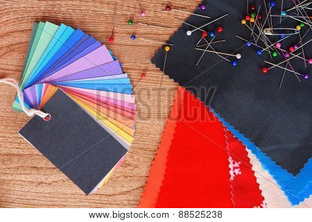 Samples of colorful fabric on wooden table, top view