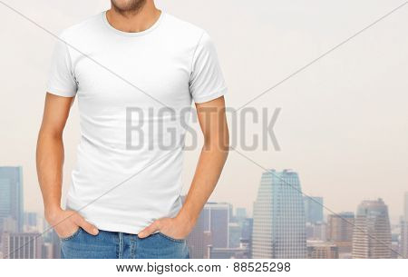 clothing design, advertisement, fashion and people concept - close up of ma in blank white t-shirt over city background