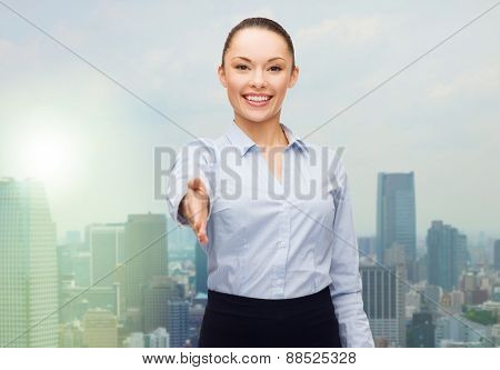 business, gesture and education concept - friendly young smiling businesswoman giving hand for handshake over city background