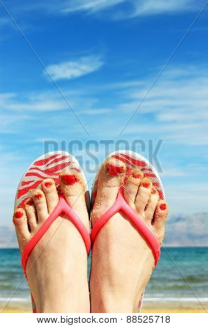 Closeup of bright flip flops and legs on sea background