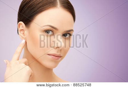 people, beauty, hearing and healthcare concept - face of beautiful woman touching her ear over violet background
