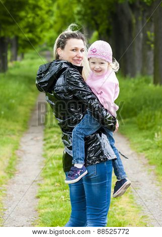 portrait of mother with her little daughter in spring alley