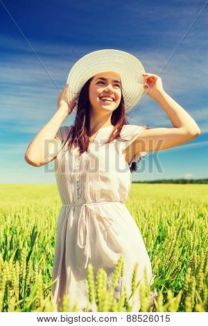 happiness, nature, summer, vacation and people concept - smiling young woman wearing straw hat on cereal field