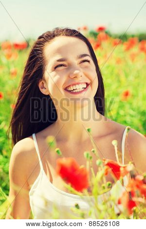 happiness, nature, summer, vacation and people concept - laughing young woman on poppy field