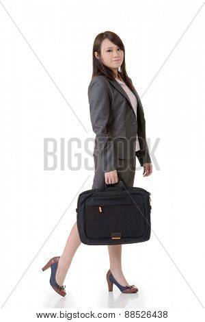 Walking business woman holding briefcase, full length portrait on white background.
