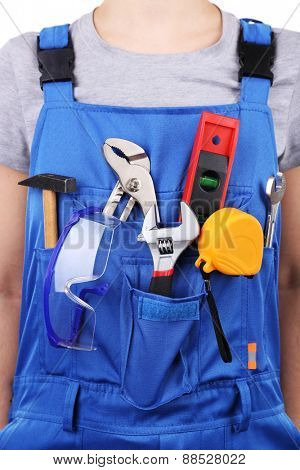 Man in coveralls with tools in his pocket, closeup