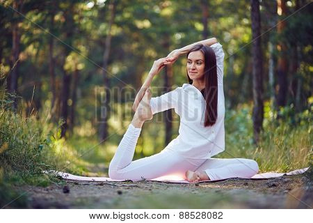Flexible woman stretching her legs and arms in park