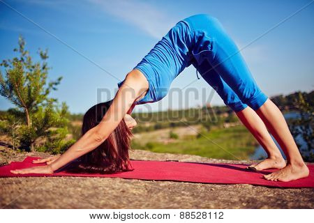 Young and fit woman practicing yoga outdoors