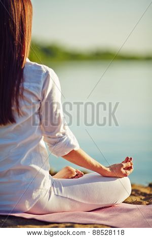 Meditating woman relaxing on coastline