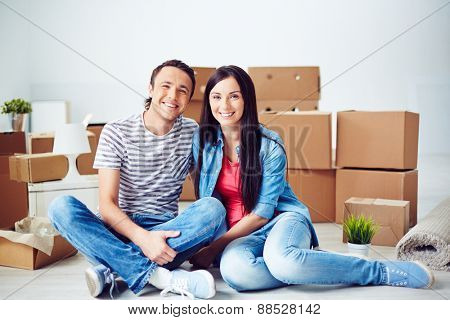 Happy young couple sitting on the floor of new flat on background of boxes