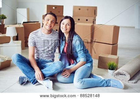 Happy man and woman sitting on the floor of new flat on background of packages