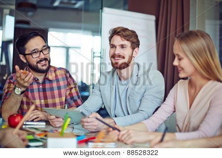 Happy businessman with touchpad and his colleagues communicating in office