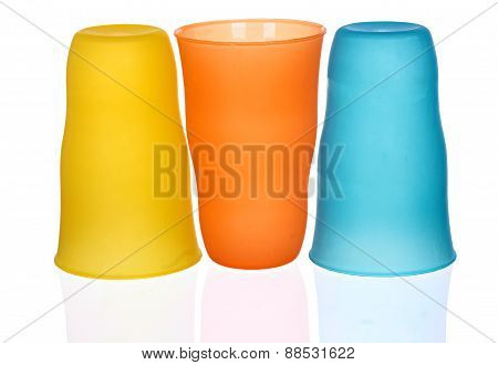 Plastic glass of various color isolated on white background