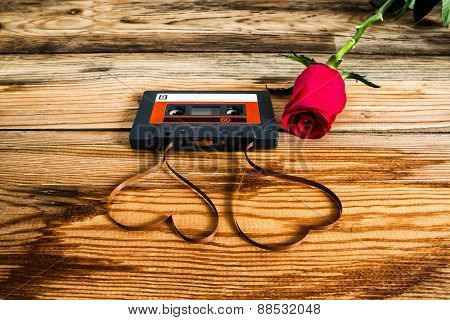 Rose And Vintage Audio Cassette With Loose Tape Shaping Two Hearts On A Wooden Background.